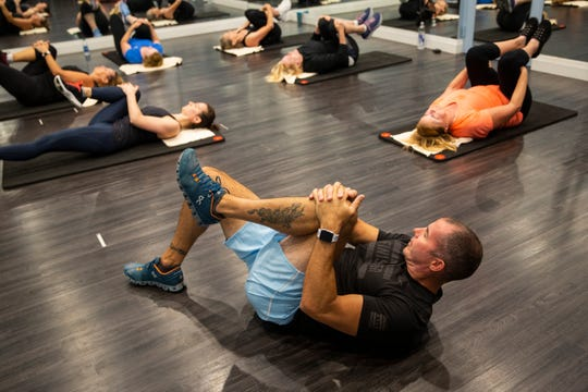 Stan Schoenewald leads his class in stretches after a TRX, or total body resistance exercise, class at Kensington Country Club fitness center in Naples on Monday, April 15, 2019.