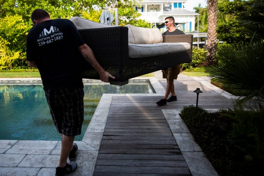 Nick Matson, right, and Kenny McAdams, left, move patio furniture being donated to Providence House, a Naples womens' shelter, from a home in Naples on Monday, April 8, 2019. McAdams and Matson are fellow graduates of the Justin's Place Recovery Program at St. Matthew's House, and McAdams is Matson's first full-time employee.