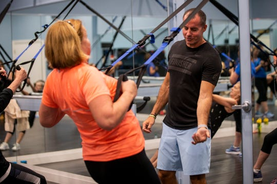 Stan Schoenewald instructs Nanette Marsh during a TRX, or total body resistance exercise, class at Kensington Country Club fitness center in Naples on Monday, April 15, 2019.
