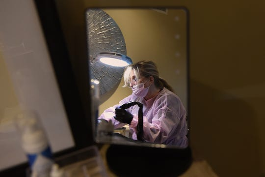 Fernicola's reflection is shown in a tabletop mirror, while she touches up a client's areola tattoo on April 17.