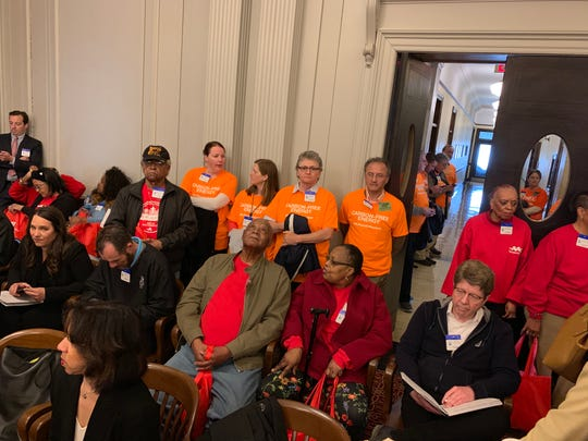 Nuclear plant workers in orange and AARP New Jersey members in red wait for the BPU meeting to begin in the Statehouse on April 18, 2019.
