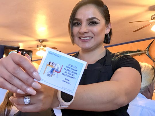 Liz Michaelson, waitress at Irma's Restaurant, displays a contingency card with the restaurant's signature dish on it.