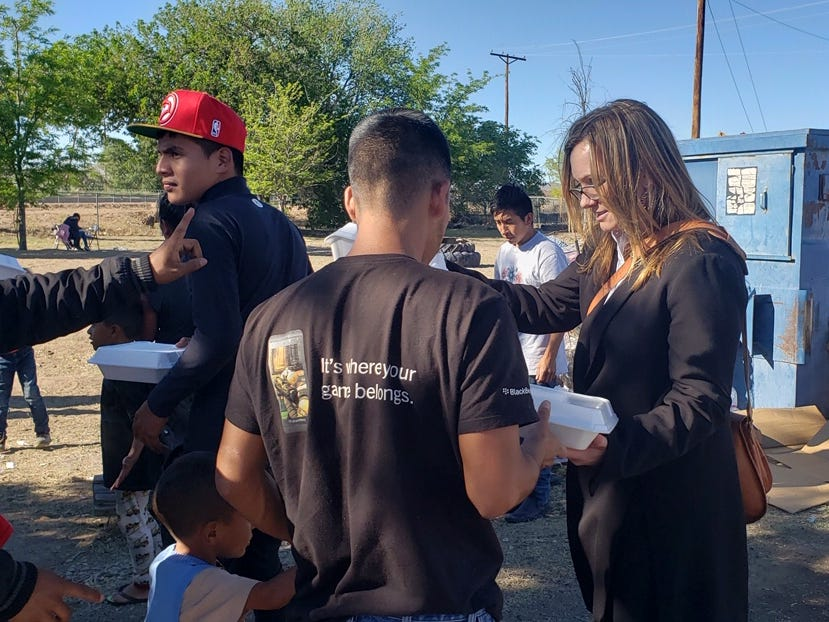 New Mexico Homeland Security and Emergency Management Secretary Jackie White hands a meal to a migrant at the Gospel Rescue Mission on