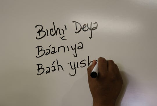 Joseph Chee writes a list of words in the Navajo language on Thursday.