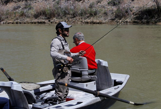 Thom Chacon, a guide with Duranglers, prepares a fishing pole for clients Thursday at Texas Hole below Navajo Dam.