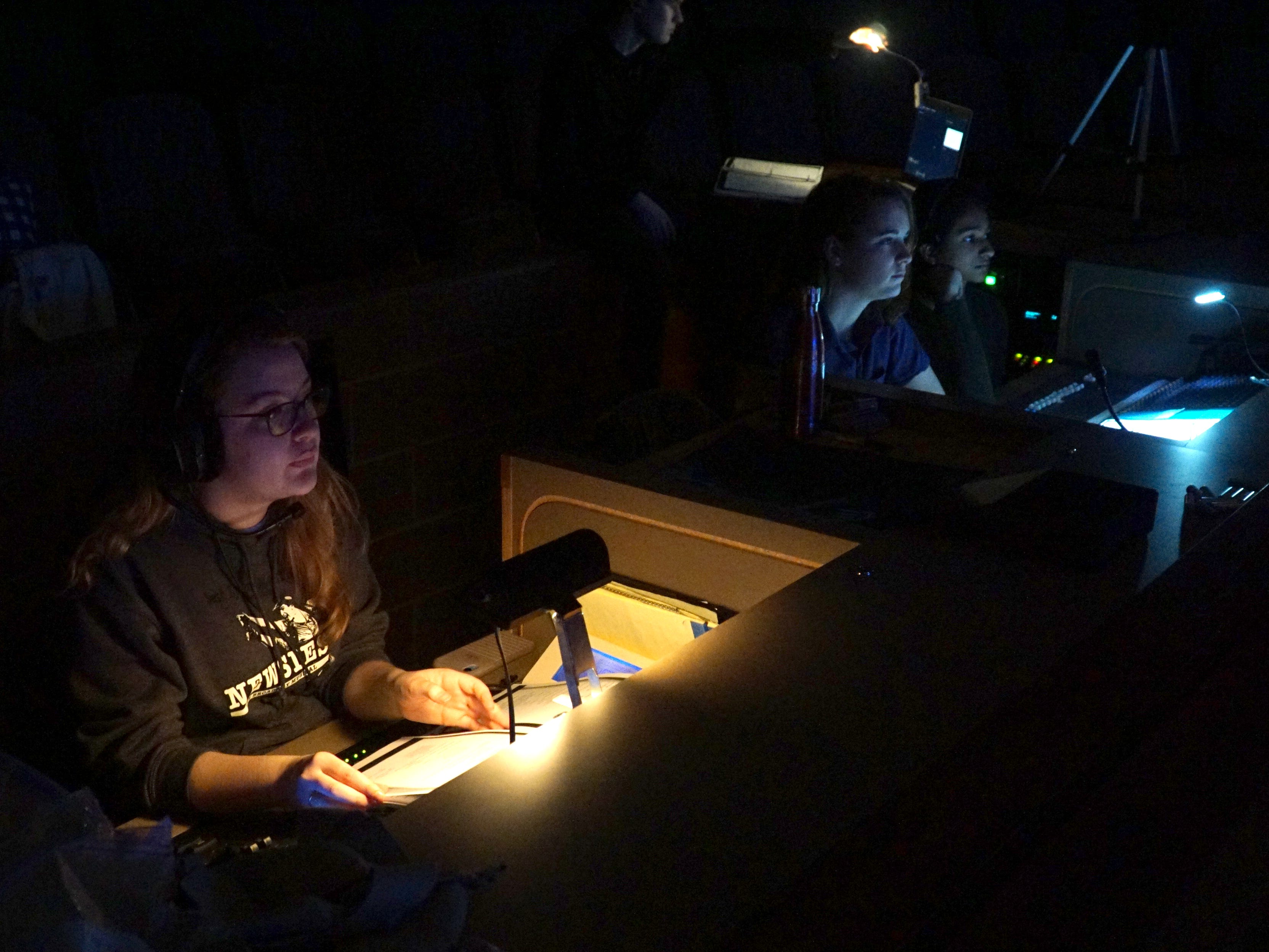 Students running the lights and sound of Newsies work on an April 18 rehearsal.