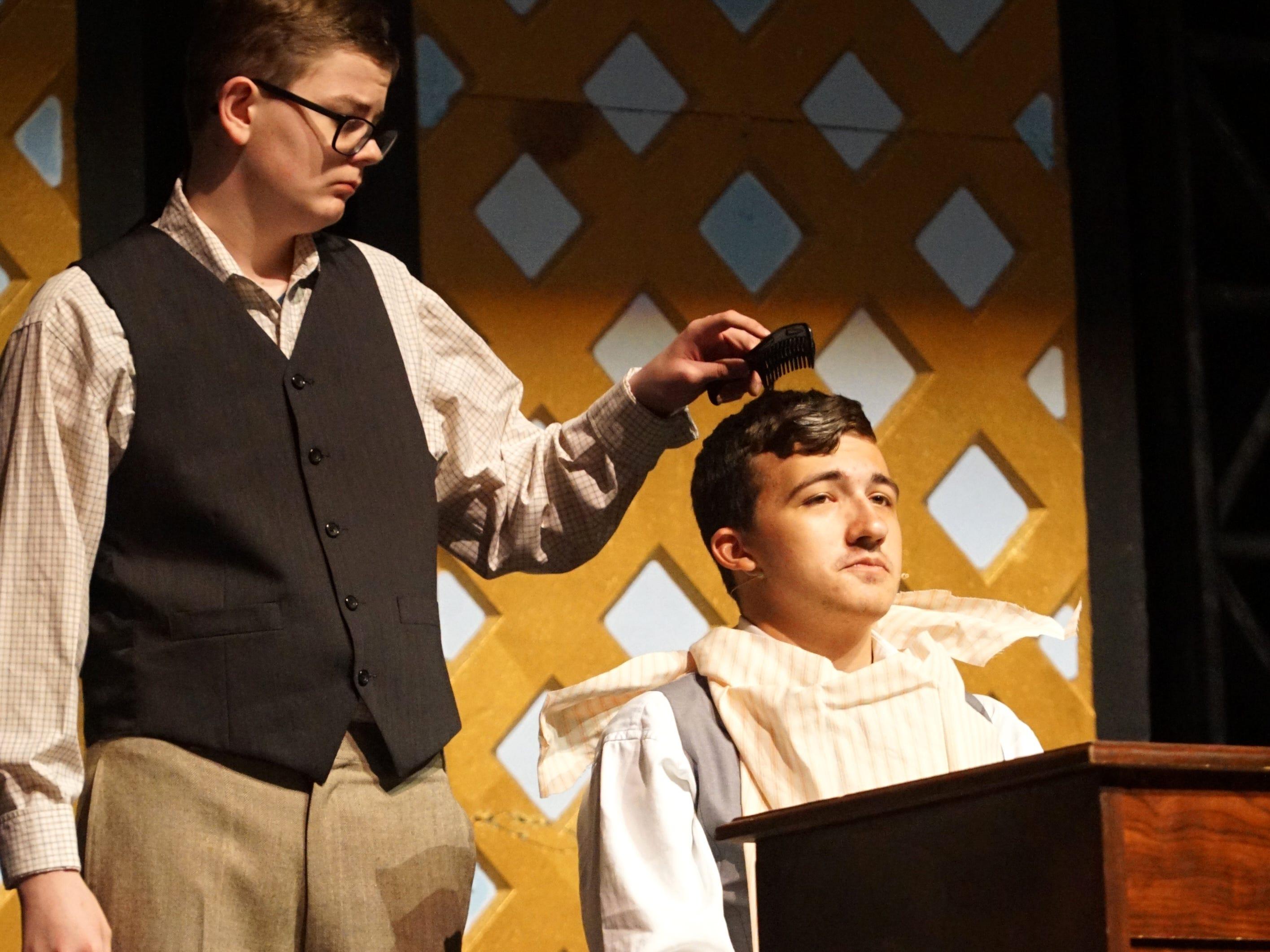 Mr. Pulitzer (Derek Portillo), right, in a rehearsal scene of South Lyon East's Newsies.