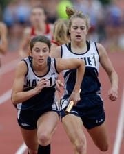 Xavier's Vanessa Laundrie takes the baton from Jessica Kwasny during the 1,600-meter relay at the WIAA Division 2 state track and field meet last June in La Crosse.