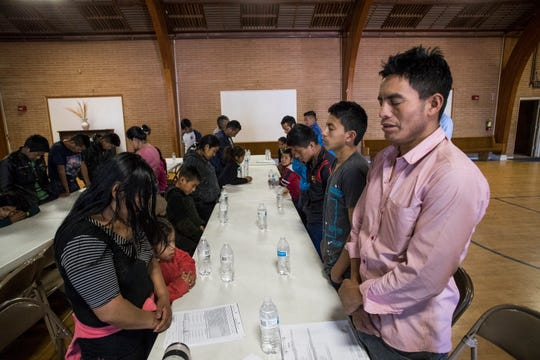 Guatemalan migrants seeking pray at Blythe's Seventh-day Adventist Church before eating breakfast. Riverside County staff picked the families up at a Greyhound bus stop and transported them to the church.