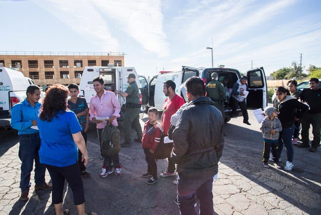 U.S. Border Patrol agents release Guatemalan asylum seekers at a Greyhound bus stop in Blythe. County officials receive the migrants and transport them to a local church.