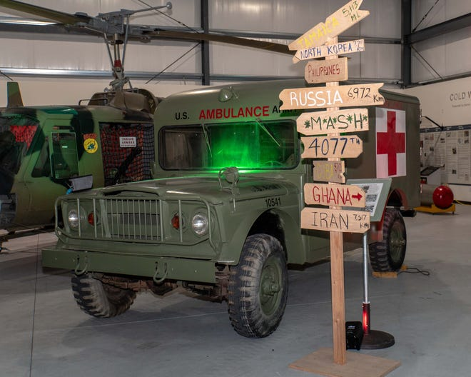 A U.S. Army ambulance, helicopter and mileage sign