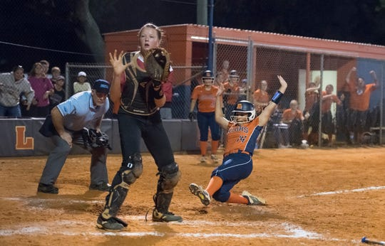Siniaya Hardy (14) slides into home for the game winning run after pitcher Avery Beauchaine (8) couldn't handle Alyssa Hart (18)'s pop up in the bottom of the 7th inning during the Tate vs Escambia softball game at Escambia High School in Pensacola on Wednesday, April 17, 2019.