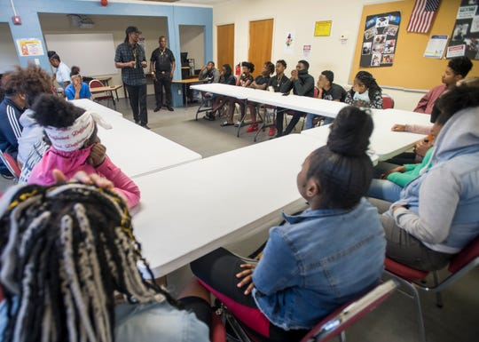 Kenneth Daggans, top center right, looks on as Pensacola NAACP Chapter President Rodney Jones talks with at-risk youth about making the right decisions and avoiding gang involvement at the Jolene Avant Center for Excellence in Pensacola on Tuesday.