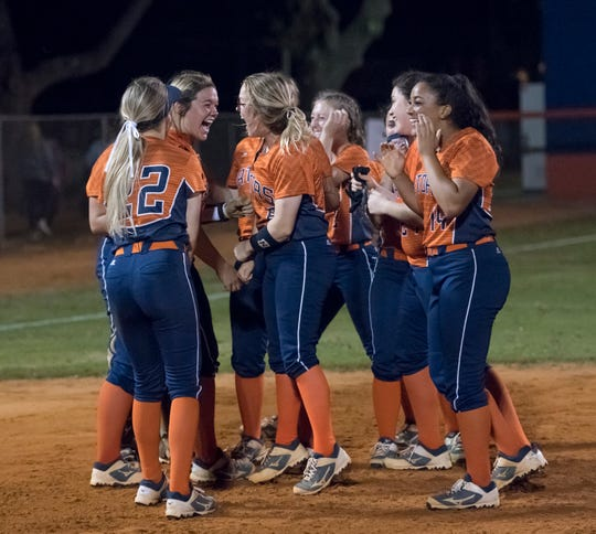 The Gators celebrate winning the coin toss determining first place in the district following their win in the Tate vs Escambia softball game at Escambia High School in Pensacola on Wednesday, April 17, 2019.