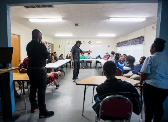 Kenneth Daggans, left, looks on as Pensacola NAACP Chapter President Rodney Jones talks with at-risk youth about making the right decisions and avoiding gang involvement at the Jolene Avant Center for Excellence in Pensacola on Tuesday.