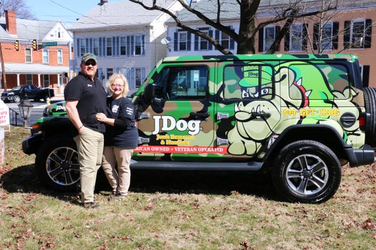 Shawn and Amy Stroop, owners of JDog Junk Removal and Hauling, in front of their branded car.
