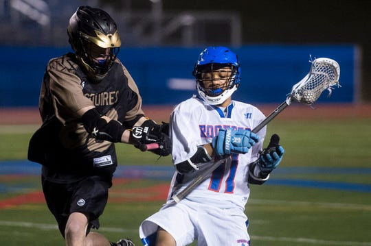 Spring Grove's Madison Moore (11) gets checked by Delone Catholic's Harry Cole during a boys' lacrosse game on Tuesday, March 28, 2017. Moore, also competing in track and field, has 51 ground balls for the Rockets this season.