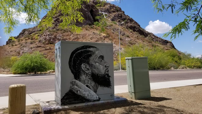 A mural honoring slain rapper Nipsey Hussle appears on the back of an electrical box near Broadway Road and 55th Street in Tempe.