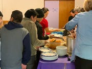 Migrant families have lunch at the former Benedictine monastery in Tucson on Feb. 28. More than 1,100 migrants that traveled as a family have passed through here in all of February.