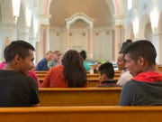 Two migrant fathers from Central America wait for the orientation to begin at the former Benedictine Monastery in Tucson on Feb. 28. The space has been operating as a shelter for asylum seeking families.