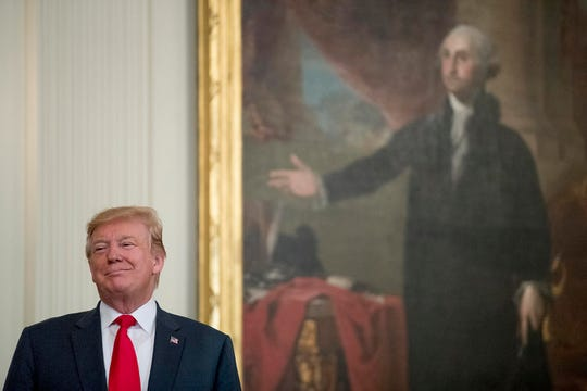 President Donald Trump stands in front of a portrait of George Washington.