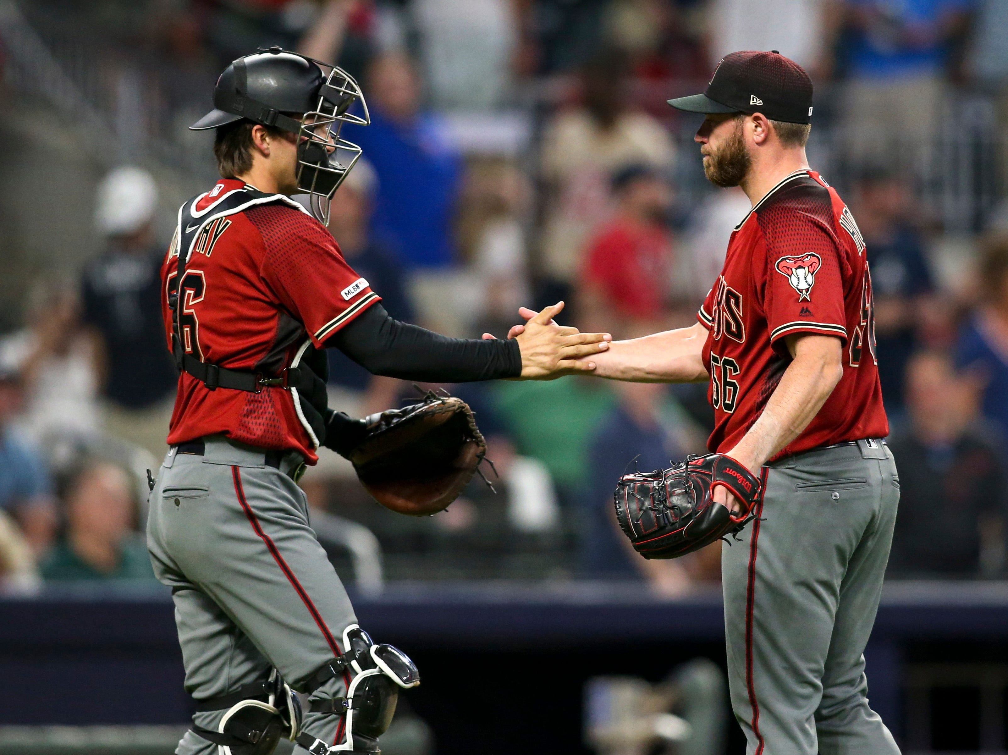 Apr 17, 2019; Atlanta, GA, USA; Arizona Diamondbacks center fielder Tim Locastro (16) and relief pitcher Greg Holland (56) celebrate after a victory against the Atlanta Braves at SunTrust Park. Mandatory Credit: Brett Davis-USA TODAY Sports
