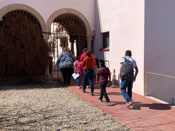Theresa Cavendish, the director of operations for Catholic Community Services, leads three families inside the former Benedictine Monastery in Tucson on Feb. 28.