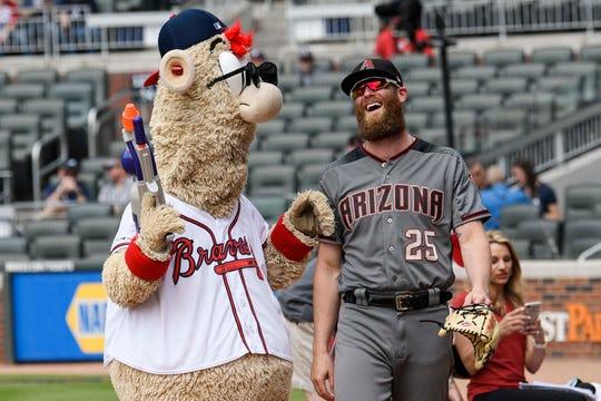Atlanta Braves mascot Blooper and Arizona Diamondbacks relief pitcher Archie Bradley (25) interact on the field prior to the game at SunTrust Park.