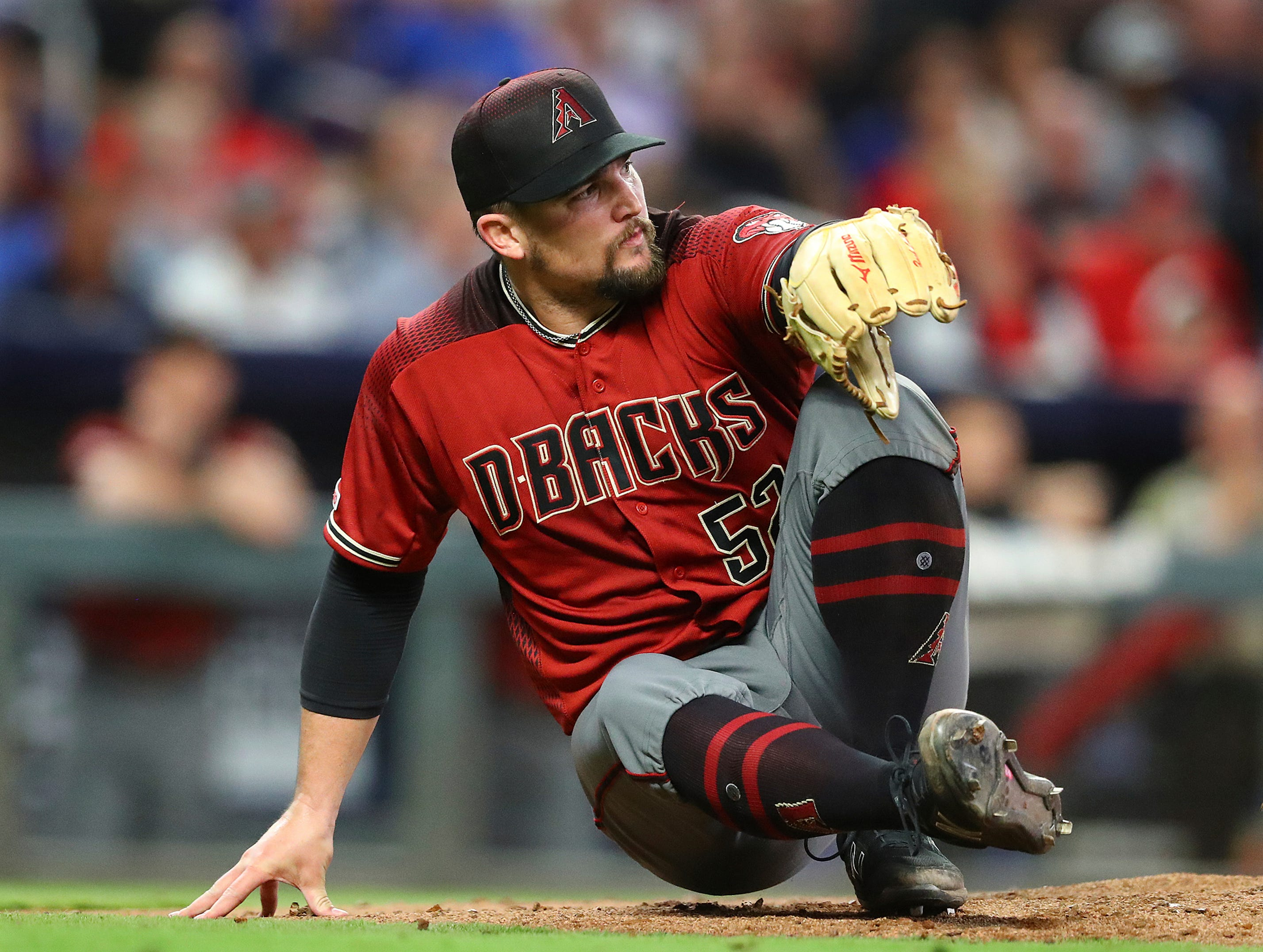 Arizona Diamondbacks pitcher Zack Godley drops to the mound to avoid a line drive by Atlanta Brave's Dansby Swanson that went for an out during the sixth inning of a baseball game Wednesday, April 17, 2019, in Atlanta. (Curtis Compton/Atlanta Journal-Constitution via AP)