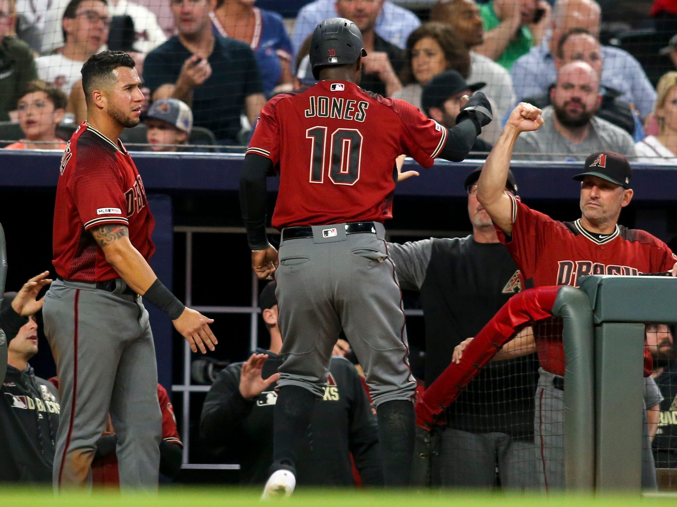 Apr 17, 2019; Atlanta, GA, USA; Arizona Diamondbacks right fielder Adam Jones (10) celebrates with manager Torey Lovullo (17) after scoring a run against the Atlanta Braves in the seventh inning at SunTrust Park. Mandatory Credit: Brett Davis-USA TODAY Sports