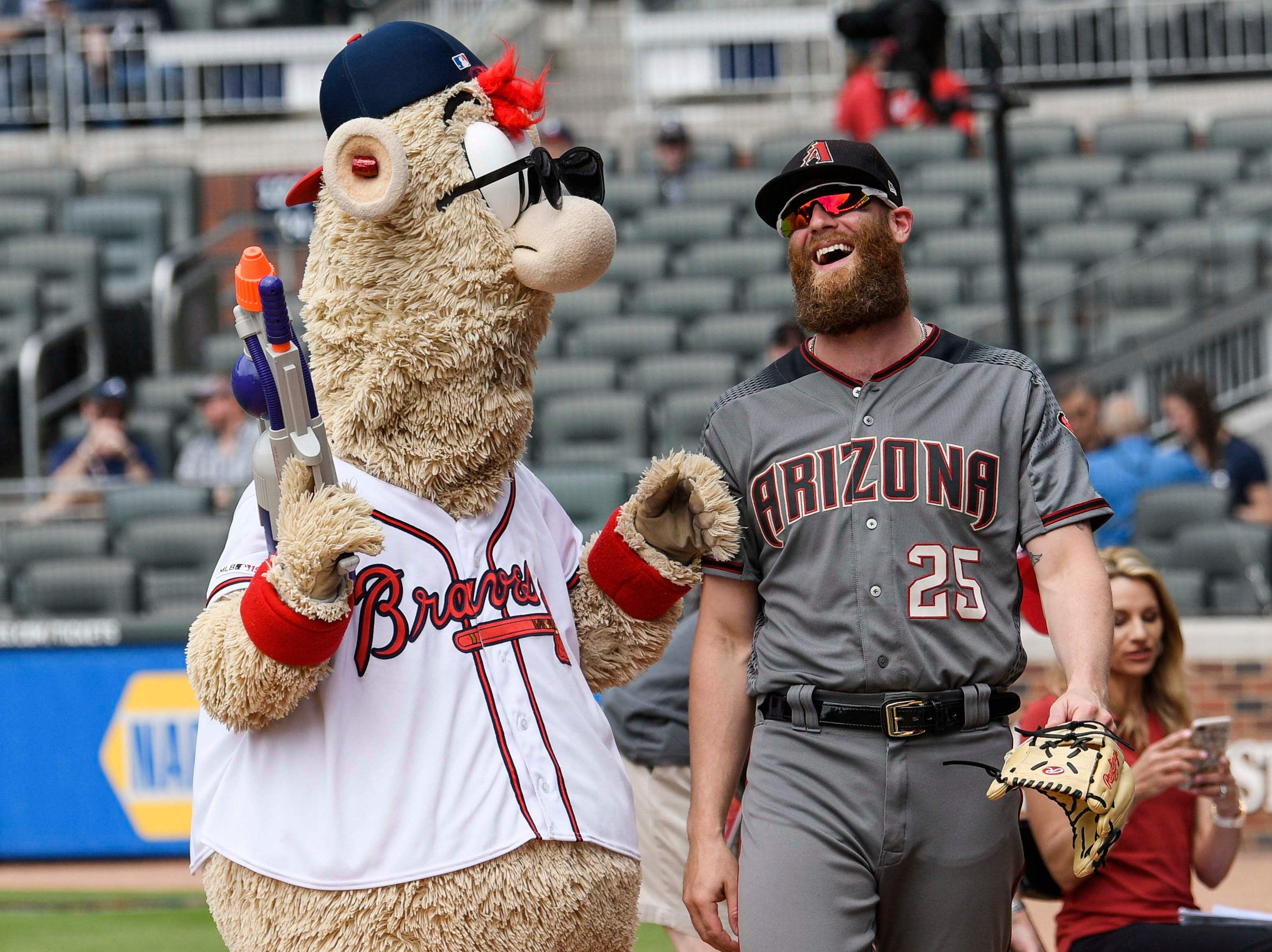 Apr 18, 2019; Atlanta, GA, USA; Atlanta Braves mascot Blooper and Arizona Diamondbacks relief pitcher Archie Bradley (25) interact on the field prior to the game at SunTrust Park. Mandatory Credit: Dale Zanine-USA TODAY Sports
