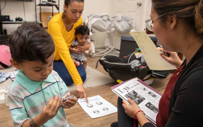 Ana Maria Rodr'guez (right) coaches Whitney Bell, a mom of three, during a recent home visit through the Healthy Families Program.