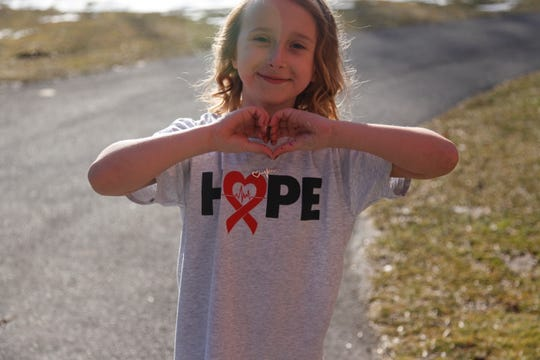 Addy Calnon shows off a T-shirt that has helped bring awareness to Long QT Syndrome, a serious heart condition she  lives with.