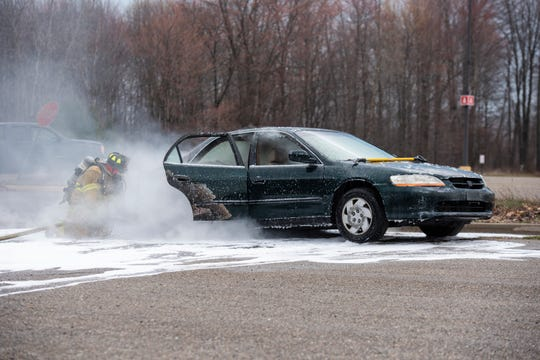 Crews work to extinguish a car fire Thursday, April 18, 2019 in a parking lot near Sam's Club in Port Huron.