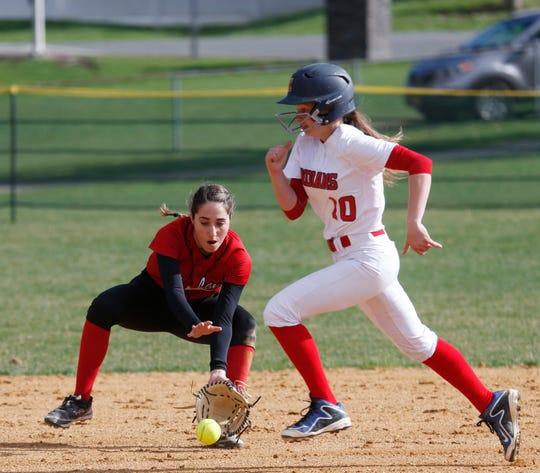 Ketcham's Alyssa Hughes sprints to third base passed Fox Lane's Adriana Piccolino recovering an infield hit during Tuesday's game on April 16, 2019.