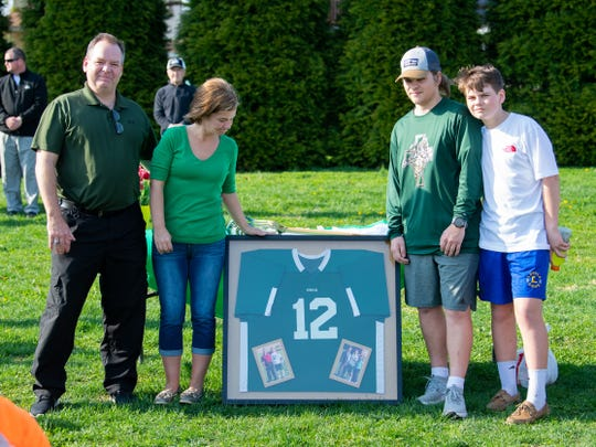 From left, John, Terry, Liam and Aidan O'Connor stand next to Brendan's old York Catholic lacrosse jersey. The team gifted it to the family during halftime of the York Catholic and York Suburban lacrosse game Thursday.