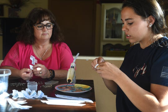 From left, Yvette Clark and Taylor Fleck make ribbons to honor the memory of friend Sunni Dicarrillo on  April 17, 2019. Dicarrillo's body was recently recovered at Silver Lake in Stead after he went missing last March.