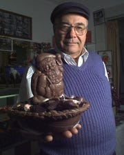 Peter Livadas, the owner of Peter's Sweet Shop on South Clinton Avenue, holds a chocolate Santa Claus in a chocolate holiday basket.