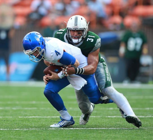 Boise State quarterback Brett Rypien (4) is sacked by  Hawaii linebacker Jahlani Tavai (31).
