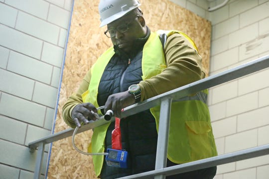 Shawn Rucker, inspector/air control project monitor, sets up an air quality control device as he works at the modernization project at East High School in Rochester Wednesday, April 3, 2019.