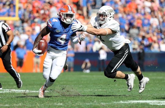 Florida Gators running back Kadarius Toney tries to escape the pursuit of   Idaho linebacker Kaden Elliss.