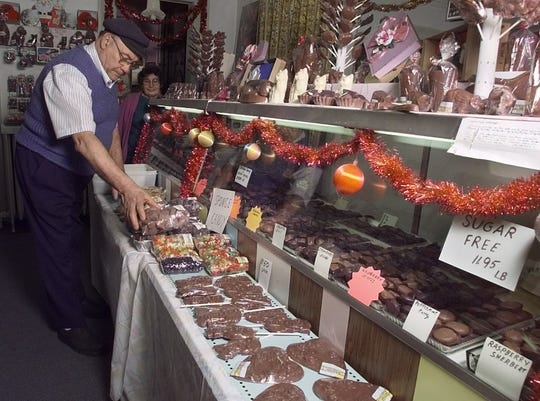 December 1998: Peter Livadas of Peter's Sweet Shop puts more chocolates out on the shelves as customers buy up his supply for the holidays.