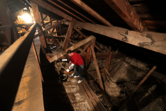 Felix Vargas, a sexton at Church of St. Luke & Simon Cyrene changes a light bulb in the attic area of the church.  The area has large wooden support beams.
