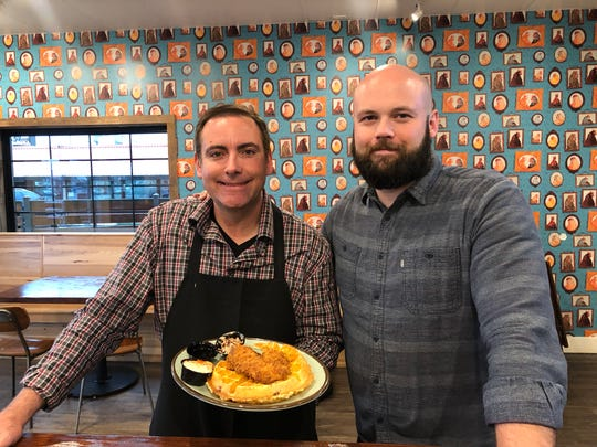 Chicken Shack owners John Dix, left, and Jonah Mills in the revamped restaurant with an order of chicken and waffle.