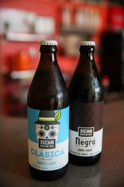 An amber lager, clásica, and dark lager, negra, are pictured bottled at Xicha Brewing in Salem on April 17, 2019.