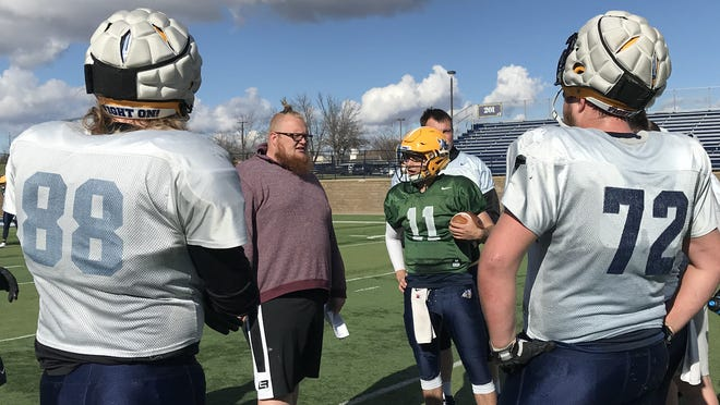 Augustana offensive line coach Matt Bacoulis talks to his players while quarterback Kyle Saddler (11) listens