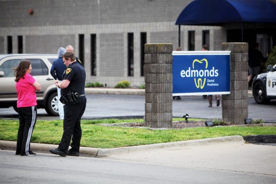 A Springfield police officer interviews a witness after an armed man allegedly entered Edmonds Dental Prosthetics April 18, 2019.