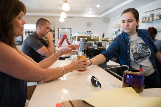 "Barista Natalie Duffield (right), of Port St. Lucie, hands a glass of fresh-brewed iced tea — served with a glass straw — to Karen Knott, of Jensen Beach, at Gilbert's Coffee Bar overlooking the south fork of the St. Lucie River on Thursday, April 18, 2019, in Stuart. Gilbert's was designated as ""ocean friendly"" by the Surfrider Foundation for their commitment to reducing plastic waste and eliminating use of expanded polystyrene (EPS) foam. Business owner Abigail Rogan said, ""For me, starting my first small business in our town and being a waterfront town, every little choice I make for Gilbert's and our brand is intentional."""