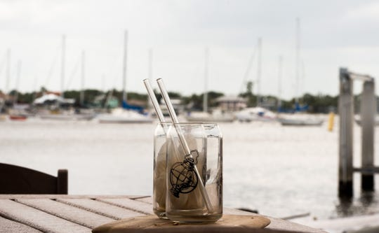 "Glass straws, like those seen here on an outside table overlooking the south fork of the St. Lucie River in Stuart on Thursday, April 18, 2019, are used for drinks served in-house at Gilbert's Coffee Bar, while ""HAY! Straws"" are used for drinks to-go."