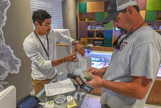 "Jimmy Walker, 50 ( right), of Fort Pierce, prepares to pay for his purchase of medical cannabis, including one of their new products, TruFlower Hybrid Lemon OG, a strain of smokable cannabis flower, from patient consultant Ryan Melo (left) on Thursday, April 18, 2019, at the Trulieve Medical Marijuana Treatment Center, 1814 Commerce Avenue in Vero Beach. ""It's just a new product, and I wanted to try the smokable,"" Walker said. ""The quality of life is better. With the smokable, I tend to get a little more relief from pain from it."" Truelieve began selling smokable cannabis in Florida, through a doctor's prescription, in March. CQ: Jimmy Walker, Ryan Melo, 1814 Commerce Avenue"